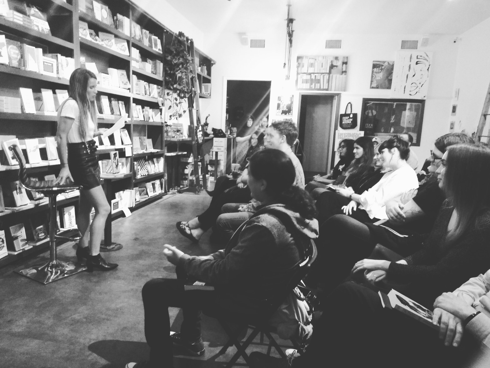 a woman stands in front of a wall of bookshelves on the left, reading from a book to two rows of listeners on the right