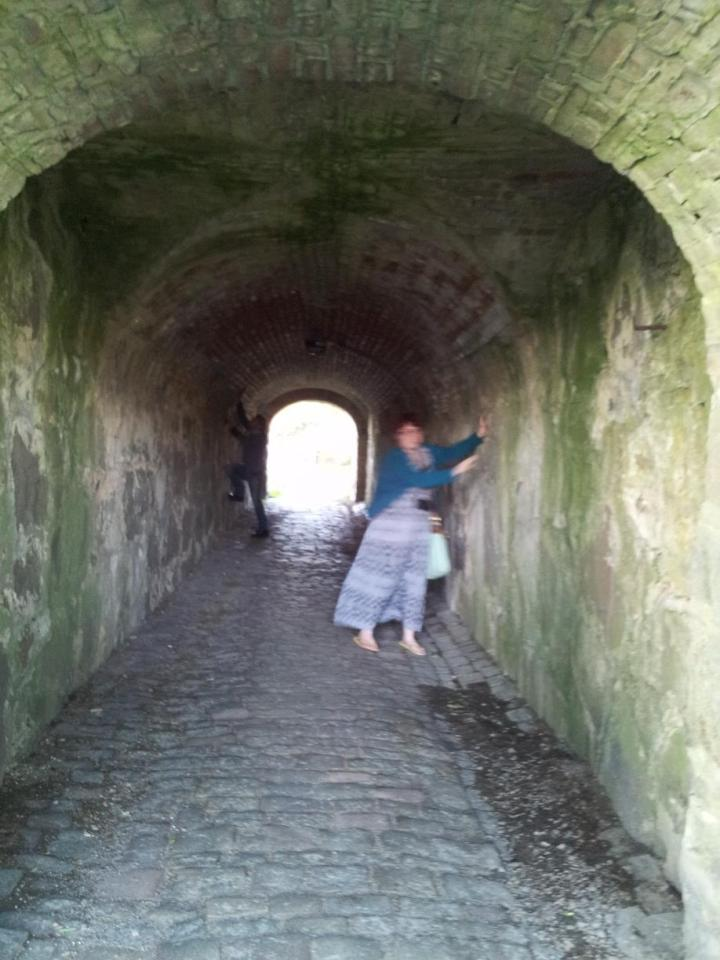 a blurry figure leans against the walls of a stone tunnel