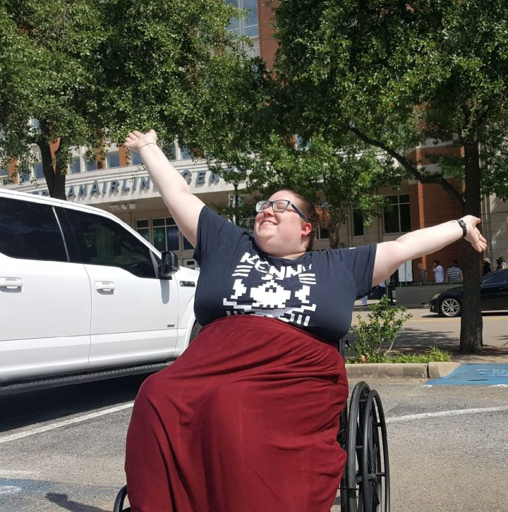 an enby femme sits in a wheelchair with their arms outstretched