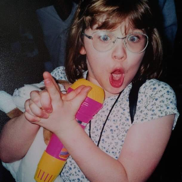 a small girl child cheering and making a goofy face